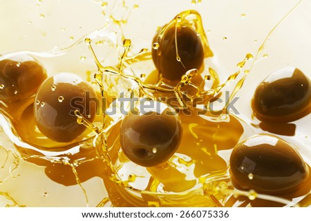 Splash of olive fruits in oil close-up view - stock photo