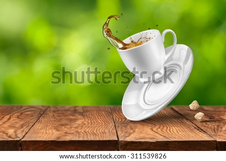 Splash of tea in the falling cup on wooden table against blurred green natural background - stock photo