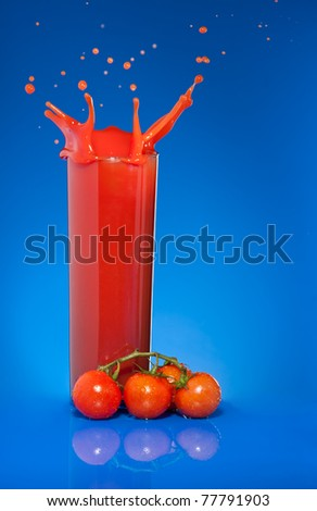 Splash of tomato juice in glass on blue background with cherry tomatoes laying nearby - stock photo
