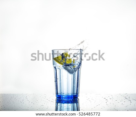 Splash of water with ice and slice of lemon in a glass on surface isolated on white