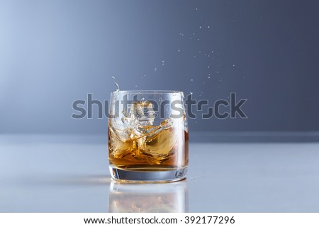 Splash of whiskey with ice  - stock photo