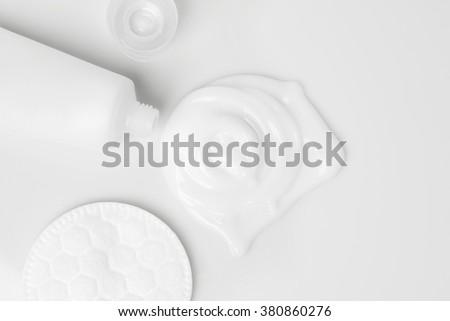 splash of white cream, tube and cosmetic cotton disk - stock photo