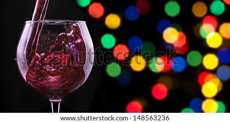 Splash red wine  against a party background on barrel with cork - stock photo