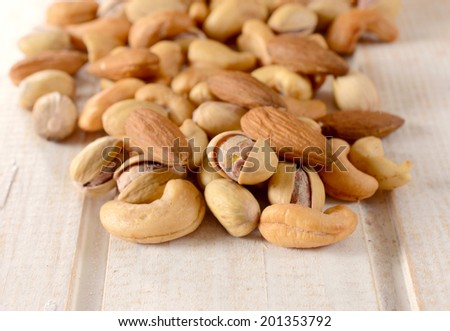 Splashed nuts mix on the wooden table.Selective focus on the front nuts - stock photo
