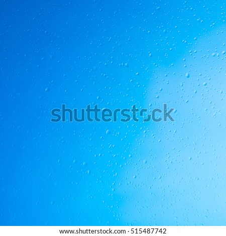 Splashes of water droplets on a blue background close-up.