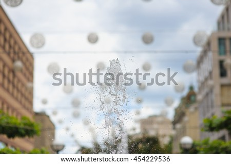 Splashes of water in city fountain. Water jet against the sky. Gush of water of a fountain. Figure from the water fountain. Jet of water in city fountain. - stock photo
