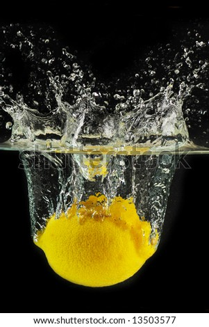 splashing lemon into a water - stock photo