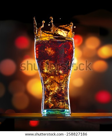 Splashing of cola with ice in glass on colorful background - stock photo