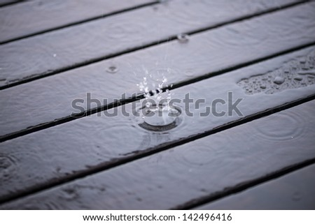 Splashing rain water droplets on wooden deck background - stock photo