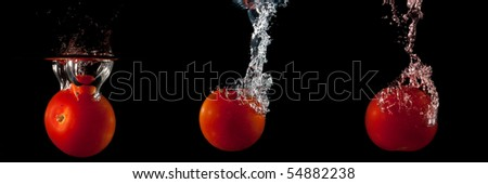 splashing tomato in to a water - stock photo