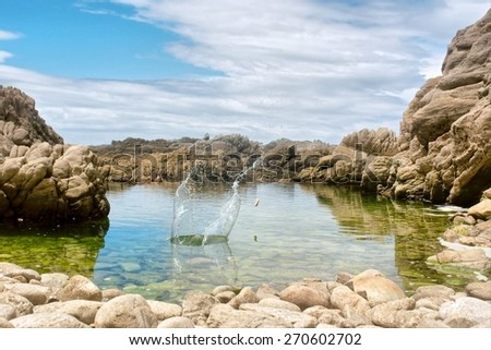 Splashing water with a rock. Shot in the Tsitsikamma National Park, Garden Route area, Western Cape, South Africa.  - stock photo