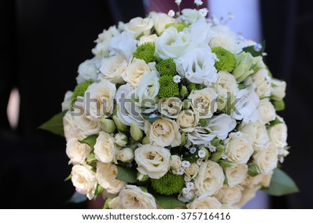 Splendid wedding bridal bouquet of champagne white colored roses and green flowers marry celebration anniversary day closeup on dark background, horizontal picture - stock photo