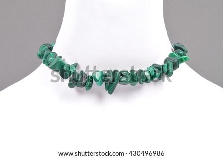 Splintered malachite chain on bust - stock photo