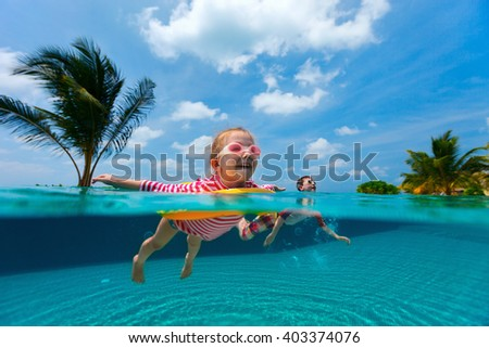 Split above and underwater photo of adorable kids having fun swimming in pool during summer vacation - stock photo