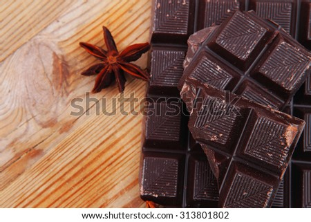 split bar of dark chocolate on wooden table - stock photo