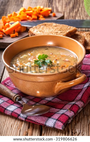 Split pea soup with sausage in a bowl. - stock photo