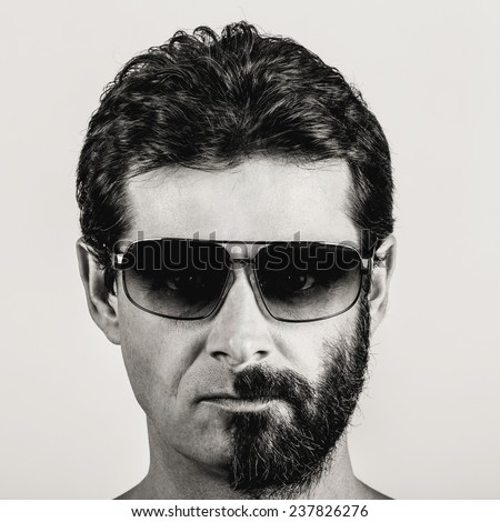 split personality - black and white portrait of man with half shaved face and sun glasses - stock photo