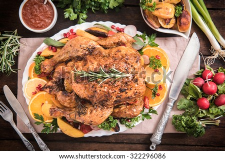 Split roasted stuffed turkey and vegetables on wooden background,from above  - stock photo