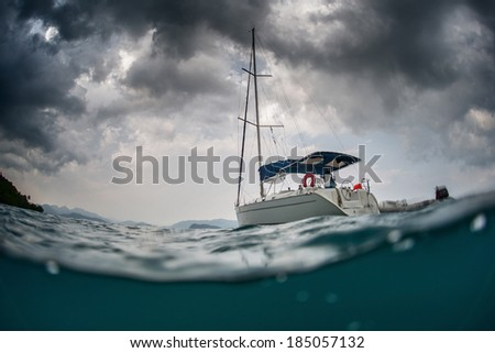 Split shot of anchored sail boat with heavy clouds in sky - stock photo