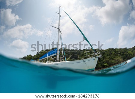 Split shot of the sail boat anchored near the green island at sunny day - stock photo