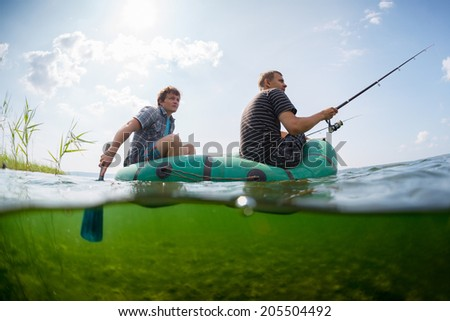 Split shot of two fishermen in the boat and underwater view of the bottom - stock photo