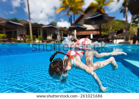 Split underwater photo of adorable little girl diving in swimming pool on summer vacation - stock photo