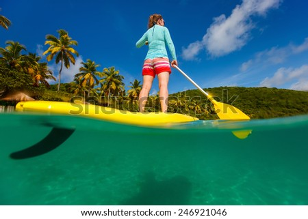 Split underwater photo of young woman on tropical beach vacation paddling on stand up board - stock photo
