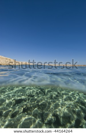 Split view of Shallow clear turquoise water with ripples of sunlight on a rocky ocean floor and blue sky and arid desert coastline. Ras Mohammed National Park Red Sea, Egypt.