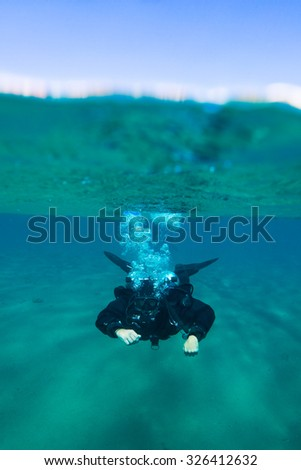Split view photo with male scuba diver swimming under water - stock photo