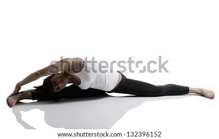 splits, portrait of sport girl doing yoga stretching exercise, studio shot in silhouette technique over white background - stock photo