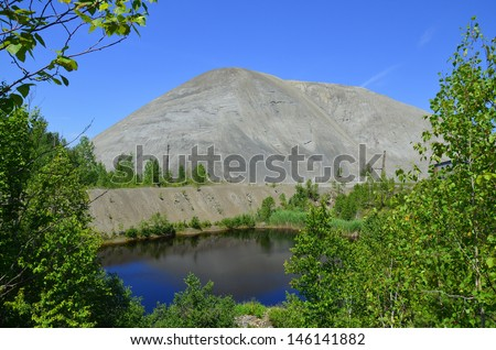 Spoil tip or boney pile, gob pile, bing, batch or pit heap is a pile built of accumulated spoil or other waste rock removed during asbestos mining. Black Lake (Thetford Mines) Quebec Canada. - stock photo
