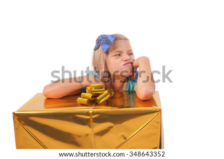 Spoiled child with gift box. She is very unhappy in spite of she just got a big present. Isolated on white. - stock photo