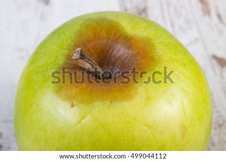 Spoiled, moldy and damaged apple on old wooden white table, unhealthy eating