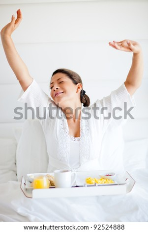 Spoiled woman having breakfast in her bed and yawning - stock photo