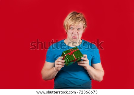 Spoiled young man holding gift on red background