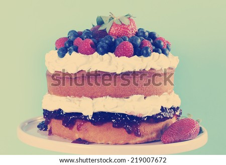 Sponge Layer Cake with fresh whipped cream, raspberry jelly and raspberries, strawberries and blueberries with retro vintage style filter. - stock photo