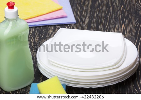 sponges, rags, dishes and a bottle of detergent - stock photo