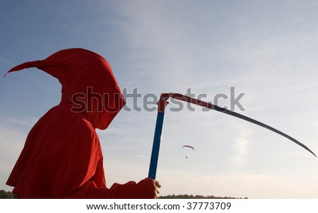 Spooky figure in red hood with a scythe waiting for flyers to come - stock photo