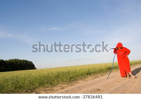 Spooky figure in red hood with a scythe waiting for someone to pass by - stock photo