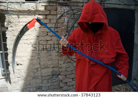 Spooky figure in red hood with scythe in the hands - stock photo