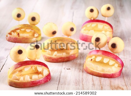 Spooky Halloween party favors or decorations made from fresh apples and dough in the form of open mouths lined with teeth topped with round googly eyes on a rustic table, creative country handicraft - stock photo