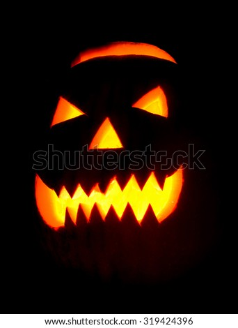 Spooky halloween pumpkin Jack O Lantern shiny inside on black