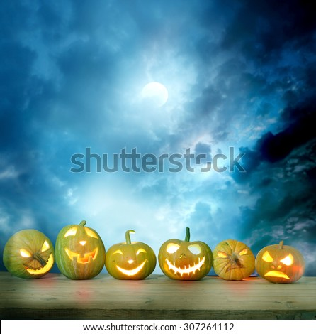 Spooky halloween pumpkins on a wooden table - stock photo