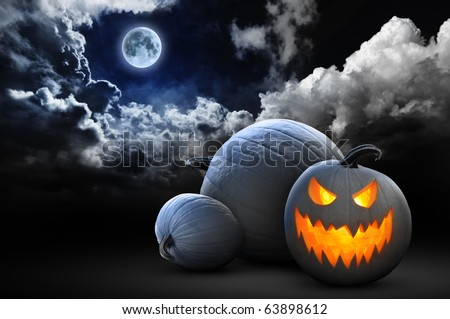 spooky halloween pumpkins under full moon - stock photo