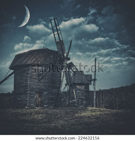 Spooky landscape with few haunted wind mills against dark forest and moody skies - stock photo