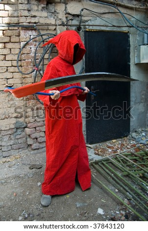 Spooky person in red hood swinging a scythe right into your face - stock photo