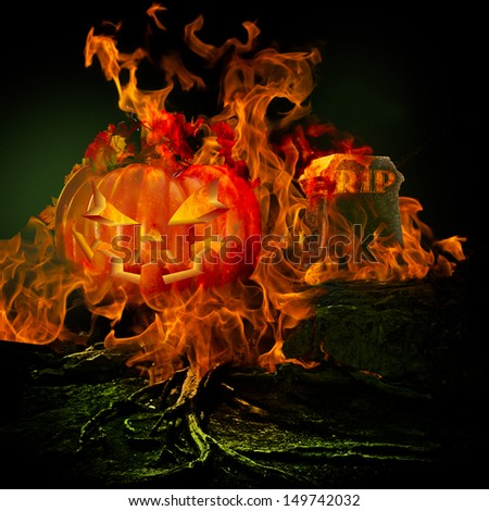 Spooky Scary Graveyard  Burning Fire Flames Fiery Pumpkin Jack O Lantern Grave Stone Rest In Peace RIP Evil Haunted Halloween Holiday Background Ghostly Orange Light Glowing Green Twisted Tree Roots  - stock photo