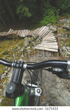 Spooky view of trail from the perspective of bike rider over handlebars. - stock photo