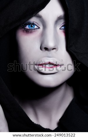 Spooky woman with intense pale face in black cape. - stock photo