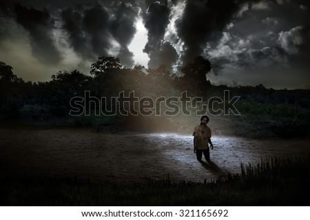 Spooky zombie standing on the creepy lake. Halloween concept - stock photo